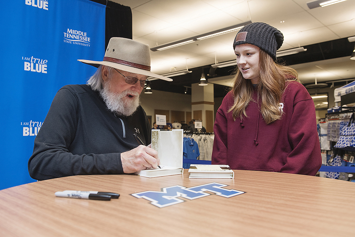 "Country Music Hall of Fame member Charlie Daniels, left, signs copies of his new inspirational book, ""Let's All Make the Day Count: The Everyday Wisdom of Charlie Daniels,"" for MTSU junior animal science major Kaylin Kirk, 21, of Fort Myers, Fla., in November 2018 at MTSU's Phillips Bookstore. Daniels, 83, died Monday, July, 6. (MTSU file photo by Andy Heidt)"