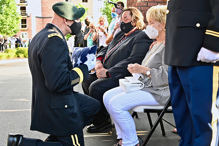 Retired Army Lt. Gen. Keith Huber, MTSU's senior advisor for veterans and leadership initiatives, kneels to present the folded American flag that had draped the coffin of country music icon Charlie Daniels to his widow, Hazel, during a memorial service Tuesday in the couple's hometown of Mt. Juliet, Tenn. Daniels, who died Monday at age 83, is patron of the university's veterans center. (MTSU photo by Andrew Oppmann)