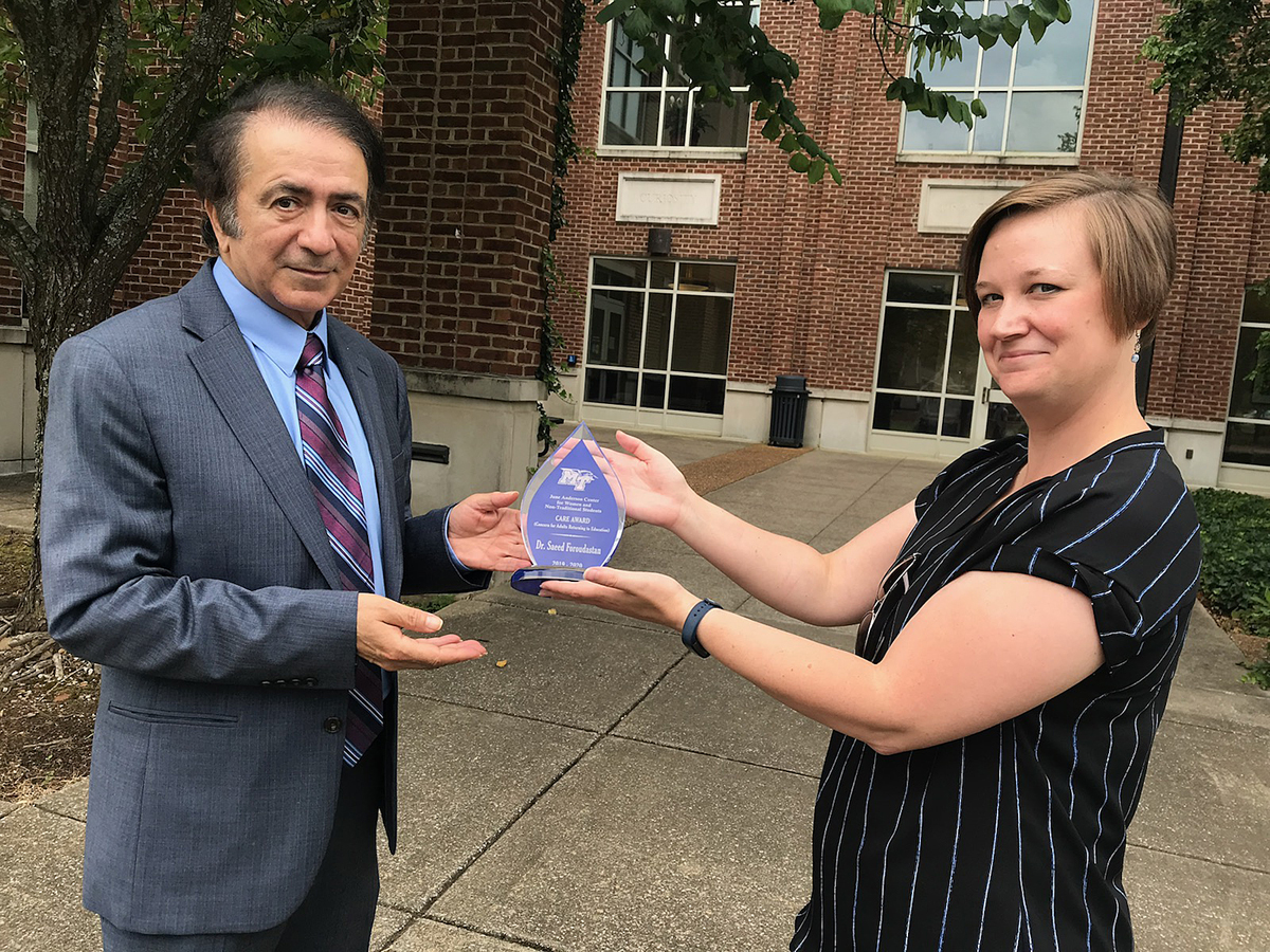 Saeed Foroudastan, left, accepts the 2020 CARE Award from Maigan Wipfli, director of the MTSU June Anderson Center for Women and Nontraditional Students, for the second straight year. The award recognizes an MTSU faculty or staff member who shows sensitivity to the diverse learning styles, experiences and multifaceted lives of nontraditional students. (MTSU photo by Randy Weiler)