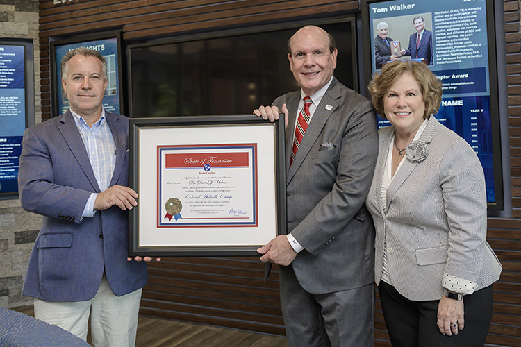 "David Urban, second from right, dean of the Jennings A. Jones College of Business MTSU, is shown with a framed certificate he was presented after recently being commissioned as a ""Colonel, Aide-de-Camp,"" which is the highest honor granted by the governor of Tennessee. It is conferred for extraordinary service to the state. Pictured inside the Business and Aerospace Building are, state Rep. Mike Sparks, left, who nominated Urban; and Urban's wife, Gina, right. (MTSU photo by Andy Heidt)"