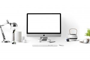 A computer and various desk accessories sit against a white background.