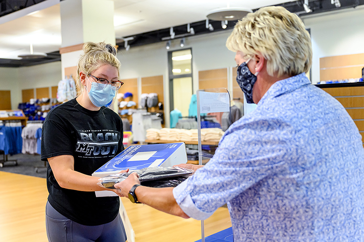 "Melisa Warner, right, assistant manager of MTSU's Phillips Bookstore, hands August graduate Kaitlyn McCord her cap and gown Friday, July 31, on the first day students could pick up their ""True Blue Graduation Box"" and commencement regalia in the Student Union. MTSU will present almost 800 summer 2020 graduates with degrees during a virtual commencement, set Saturday, Aug. 8, to celebrate their accomplishments. (MTSU photo by J. Intintoli)"