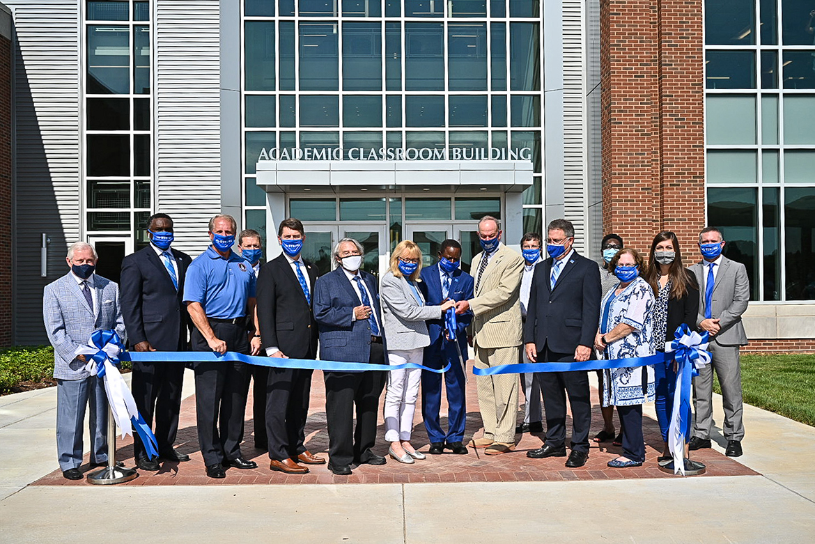 "MTSU administrators and faculty cut the ribbon in front of the university's new Academic Classroom Building Aug. 18. From left, J. D. Baker, MTSU Trustee; Darrell Freeman, vice chair, MTSU Board of Trustees; Bill Ketron, Rutherford County Mayor; Pete Delay, MTSU Trustee; Harold ""Terry"" Whiteside,"" dean, College of Behavioral and Health Sciences; Pam Wright, MTSU Trustee; Sidney A. McPhee, MTSU president; Steven Smith, chair, MTSU Board of Trustees; Greg Schmidt, chair, Department of Psychology; Mark Byrnes, MTSU Provost; Cathy McElderry, chair, Department of Social Work; Mary Martin, MTSU Faculty Trustee; Delanie McDonald, MTSU Student Trustee; and Lee Wade, chair, Department of Criminal Justice. (MTSU photo by J. Intintoli)"
