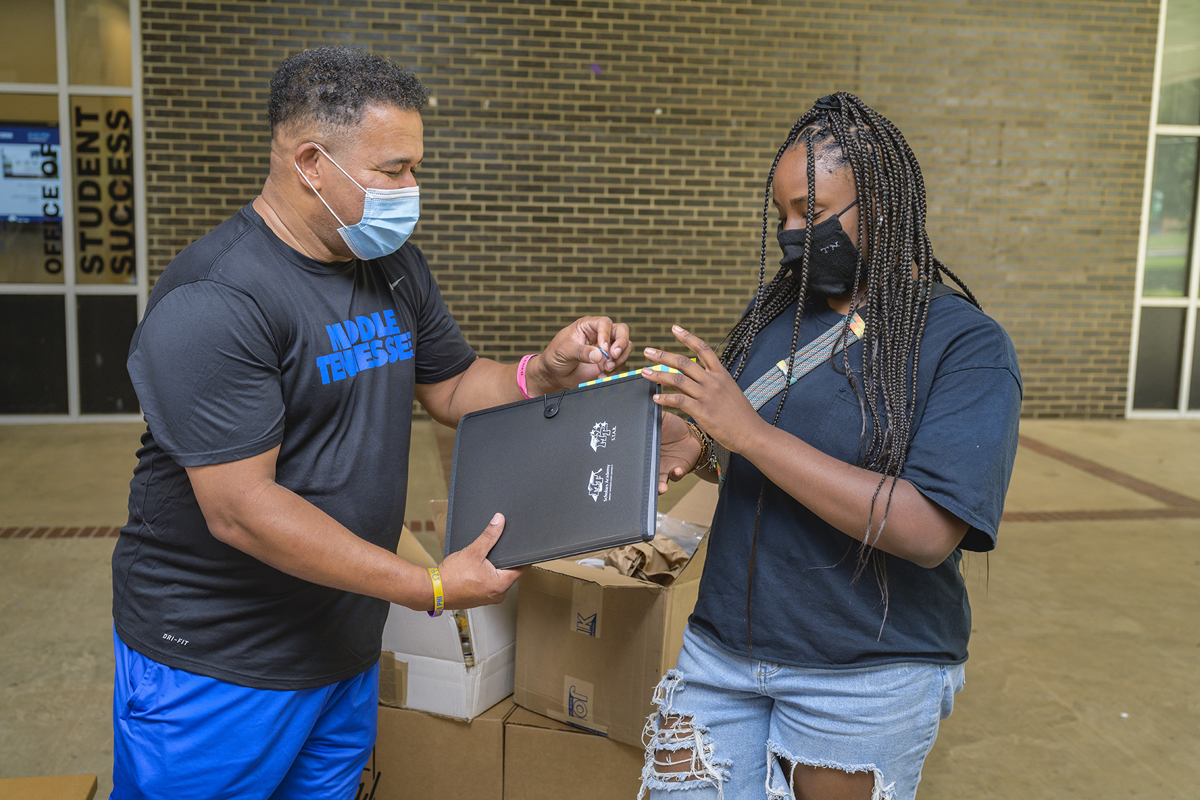 Office of Student Success staff member Marvin Spencer, left, hands out gifts to Joy Griffin of Knoxville, Tenn., at Peck Hall recently following the end of this year's virtual Freshmen Summer Institute. Nearly 100 freshmen participated, jump-starting their college careers. (MTSU photo by Andy Heidt)