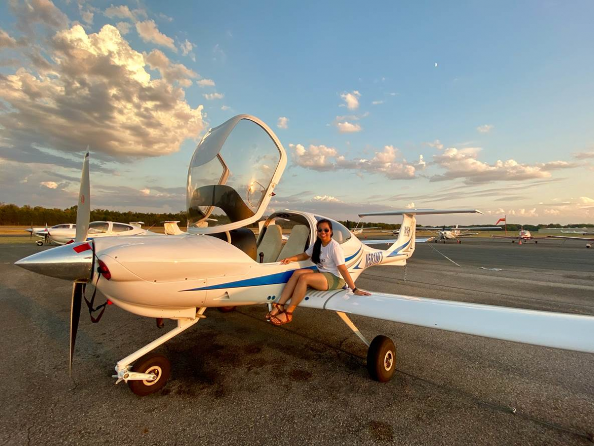 Nakanya Rodruepid, an MTSU senior from Chiang Mai, Thailand, who's majoring in aerospace, sits on the wing of a small airplane. Roduepid is an MTSU international student ambassador, one of several students from other countries who volunteer to help new international students become adjusted to their new surroundings. (Photo submitted)