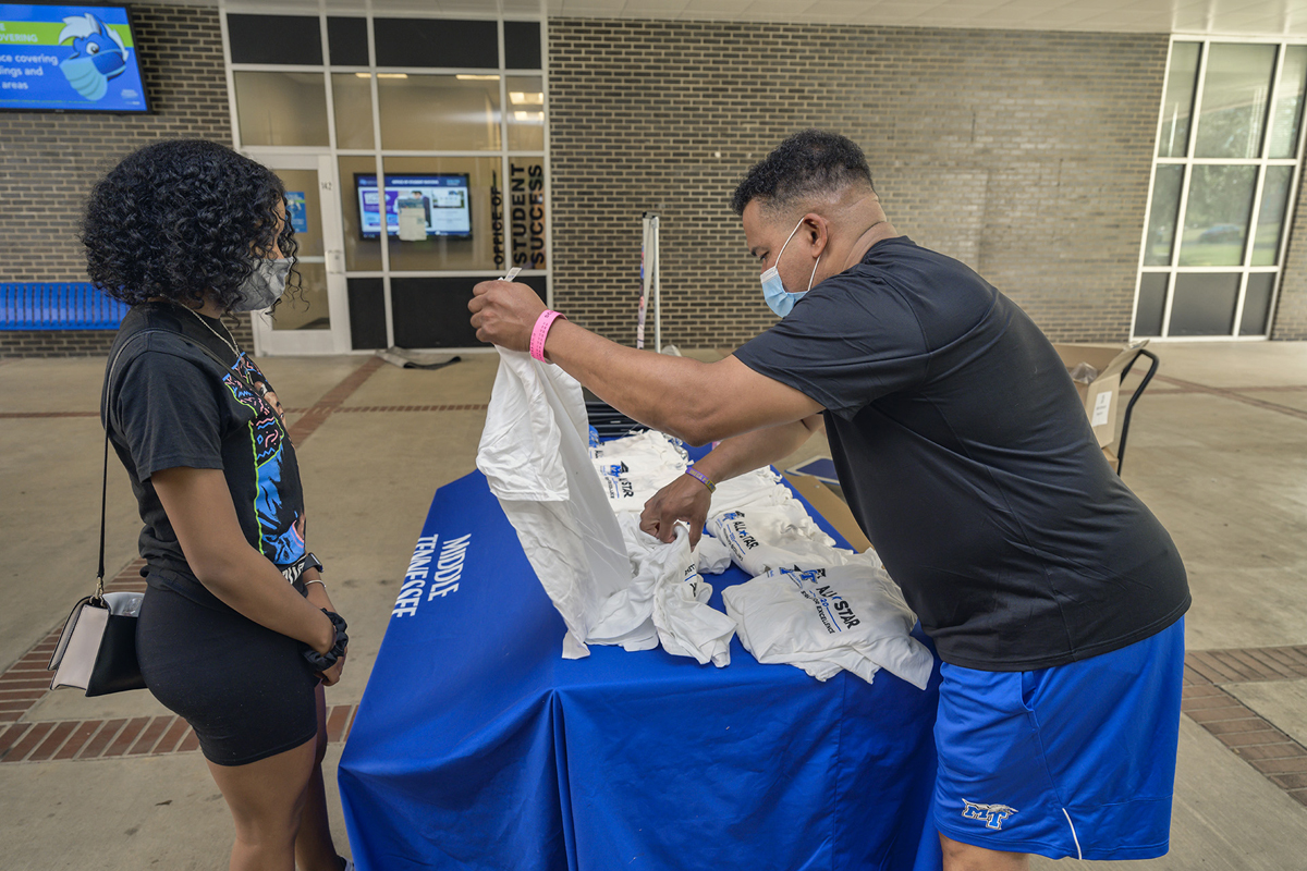 MTSU senior Tamia Hambrick, left, of Antioch, Tenn., a 2020 Scholars Academy peer mentor, receives a T-shirt for her program participation from staff member Marvin Spencer, during a recent gift giveaway for freshmen and mentors outside of the Office of Student Success in Peck Hall. (MTSU photo by Andy Heidt)