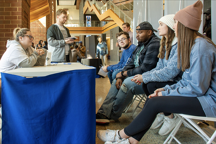 "MTSU public relations students Hannah Field, left, of Murfreesboro, and Grant Thompson, standing, a Shelbyville, Tenn., native who now lives in Antioch, Tenn., talk with fellow students about the First Amendment in the Student Union during their award-winning November 2019 ""1 for All @ MTSU: Freedom Comes First"" public relations campaign. The ""free lunch"" event let participants choose whether to temporarily trade their five First Amendment freedoms for a chicken sandwich. The nine-member student team recently received two 2020 Parthenon Awards from the Nashville chapter of the Public Relations Society of America for their ""shoestring budget"" project. (Photo submitted)"