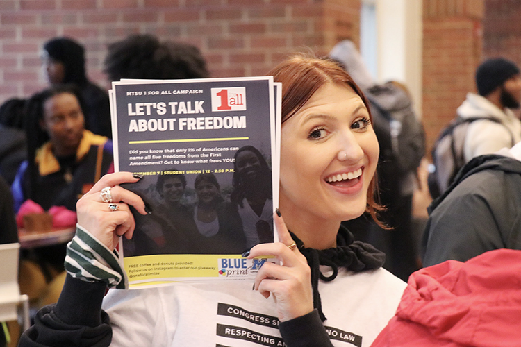 "MTSU public relations student Katelyn Compton of Nolensville, Tennessee, displays one of the flyers from her class's award-winning ""1 for All @ MTSU: Freedom Comes First"" campaign inside the Student Union in this November 2019 photo. Compton, who received her bachelor's degree last December, and her eight classmates developed the plan to educate their peers about the First Amendment and recently received two 2020 Parthenon Awards from the Nashville chapter of the Public Relations Society of America for their ""shoestring budget"" project. (Photo submitted)"