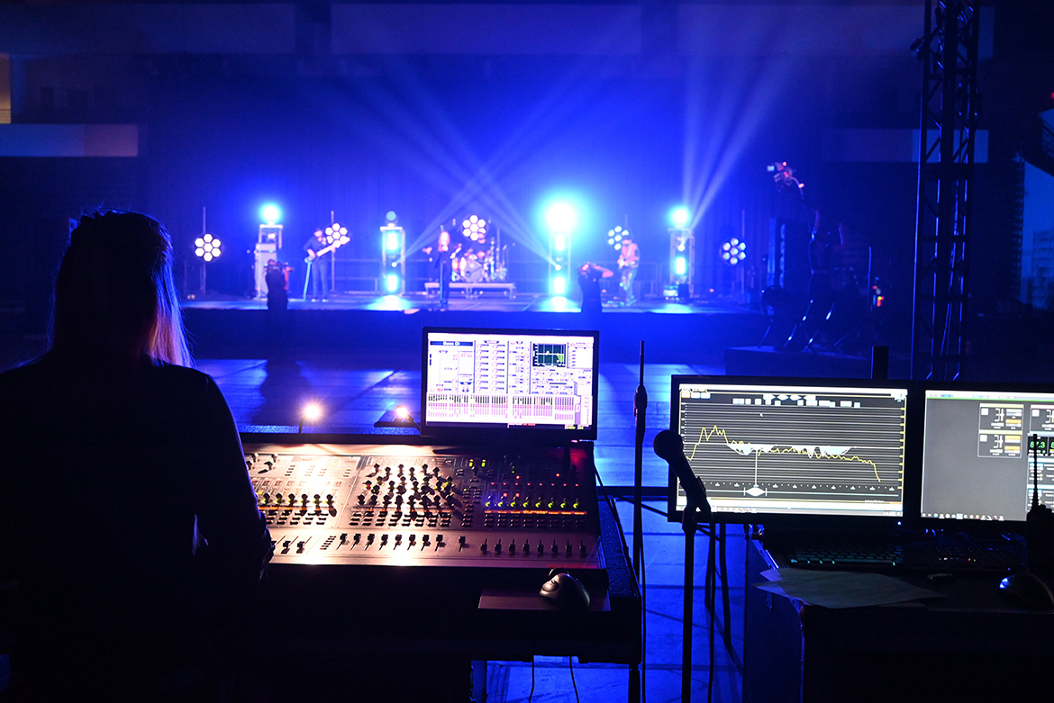 """MTSU audio production alumna Ashley Mills, left, a West Virginia native who now lives in Franklin, Tenn., operates the soundboard during with the performance of indie rock/pop band Shelter Cove on Sept. 15 at Belmont University in Nashville, Tenn. The band, which includes MTSU students and alumni who perform on the university's student-run label, Match Records, performed with artists from four other Nashville-area universities in """"Rock the Vote at Belmont University: Nashville Colleges Celebrate Democracy"""" that aired Tuesday, Sept. 22. (MTSU photo by Frank Baird)"""
