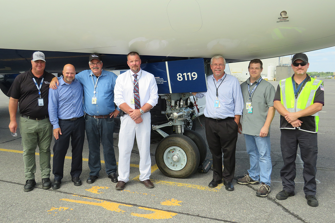 MTSU alumnus Chad Goddard, fourth from left, poses with co-workers next to a Delta Air Lines aircraft in Atlanta. Goddard, Delta's senior program manager for cabin maintenance, returned to MTSU after two decades to complete his bachelor's degree in liberal studies in Spring 2019 and is currently working on his master's in strategic leadership through MTSU Online. (Submitted photo)