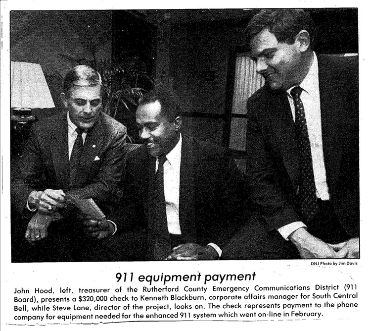 In this 1989 clipping from The Daily News Journal, John Hood, left, treasurer of the Rutherford County Emergency Communications District (911 Board) presents a $320,000 check to Kenneth Blackburn, corporate affairs manager for South Central Bell, while Steve Lane, director of the project, looks on. The check represents payment to the phone company for equipment needed for the enhanced 911 system which went on-line in February. (Courtesy of the Rutherford County Mayor's Office)