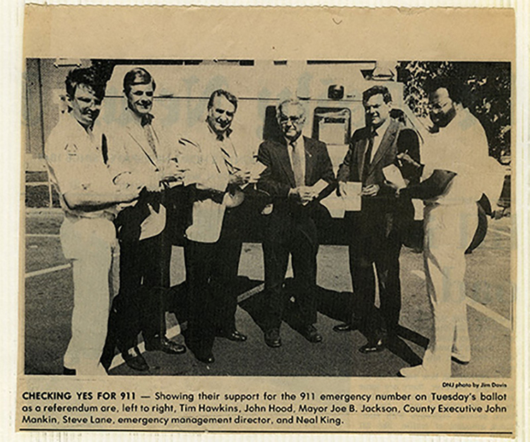 In this undated newspaper clipping from The Daily News Journal, pictured, from left, are Tim Hawkins, John Hood, Mayor Joe B. Jackson, County Executive John Mankin, Steve Lane, emergency management director, and Neal King showing their support for the 911 emergency number on the ballot as a referendum. (Courtesy of the Rutherford County Mayor's Office)
