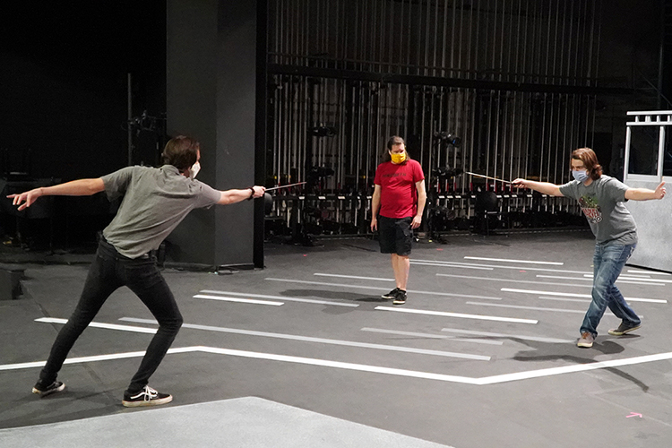 "MTSU Department of Theatre and Dance lecturer David Wilkerson, center, watches closely as junior Geo Sekeres of Goodlettsville, Tenn., left, who portrays Mercutio, duels with senior Luke McGuire of College Grove, Tenn., who portrays Tybalt, during rehearsals for the university's Oct. 1-4 production of William Shakespeare's ""Romeo and Juliet."" The production will air live from Tucker Theatre at MTSU.edu/live, the True Blue TV channel and the MTSU and MTSU Theatre Facebook Live sites. A few free in-person tickets are also available for students. (MTSU Department of Theatre and Dance photo)"