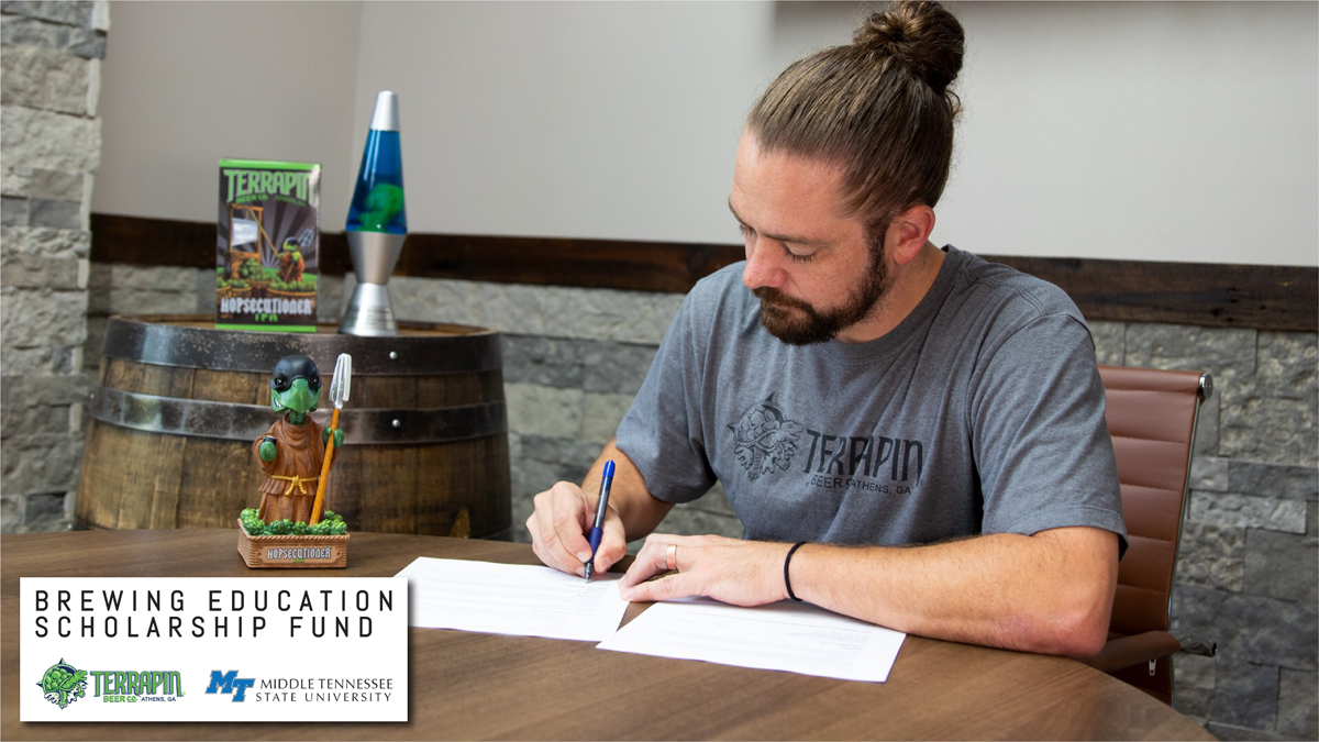"Terrapin Beer Co. President Dustin Watts signs the agreements establishing a $10,000 scholarship to underrepresented undergraduate students wanting to pursue a degree in fermentation science at MTSU. ""We want to grow diversity within Terrapin and within the brewing industry as a whole,"" he said. (Photo submitted by Terrapin Beer Co.)"