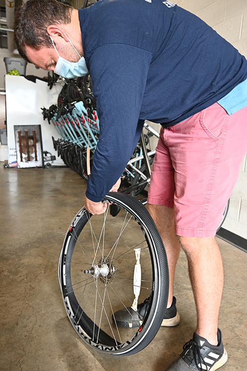 David Candeto, and understraduate construction management student, fixes a tire while working at the campus bike shop.