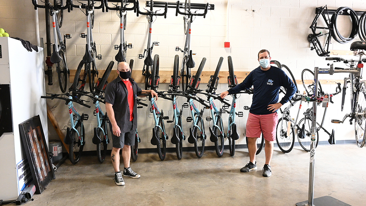 Bike shop employees, left, Elden Winkelman, and, right, David Candeto, pose in front of MTSU's available rental bikes. (MTSU photo by Stephanie Barrette)