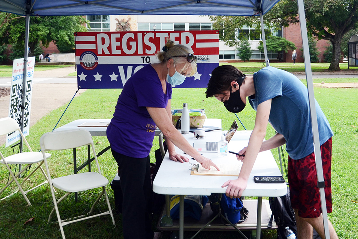Andrew Lickman, right, a freshman computer science major from Lynn Haven, Florida, registers to vote at a voter registration tent on the south side of MTSU's Peck Hall. Volunteer and MTSU alumna Lee Anne Carmack of the Murfreesboro chapter of the American Association of University Women handles the paperwork and provides information. (MTSU photo)
