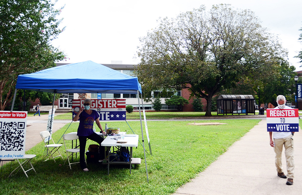 Retired Army Maj. Steve Daugherty, right, awaits members of the campus community outside the American Democracy Project's voter registration tent on the south side of MTSU's Peck Hall. Volunteer and MTSU alumna Lee Anne Carmack of the Murfreesboro chapter of the American Association of University Women is under the awning. (MTSU photo by Gina Logue)