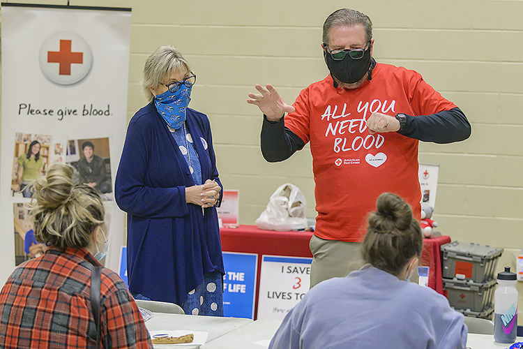 """Ray Wiley, right, MTSU Campus Recreation associate director, encourages volunteers at MTSU's three-day """"Bleed Blue to Beat the COVID-19 Blues"""" blood drive while Senior Associate Athletic Director Diane Turnham, left, listens Sept. 29 at the neighboring North Boulevard Church of Christ gymnasium. Wiley and Turnham, both longtime American Red Cross blood donors, also are part of the university's annual Bleed Blue blood drive committee. MTSU supporters donated 269 units of blood during this year's event, potentially helping up to 765 more people across Tennessee and parts of Kentucky, Illinois and Missouri. (MTSU photo by Andy Heidt)"""