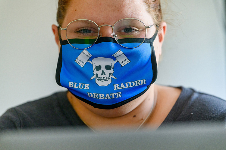 Miura Rempis, a senior political science major from Gallatin, Tennessee, displays the MTSU Debate Team's mask. The team is debating via computer due to the COVID-19 pandemic. (MTSU photo by J. Intintoli)