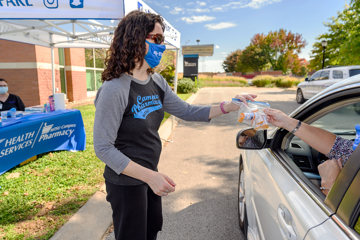 Lisa Schrader, left, director of Health Promotion at MTSU, takes unwanted medications dropped off by Kristin Wells, who works in the Office of Development, Thursday, Oct. 22, at the MTSU Drug Take Back Day at the pharmacy drive-thru at the Student Health, Wellness and Recreation Center. (MTSU photo by J. Intintoli)