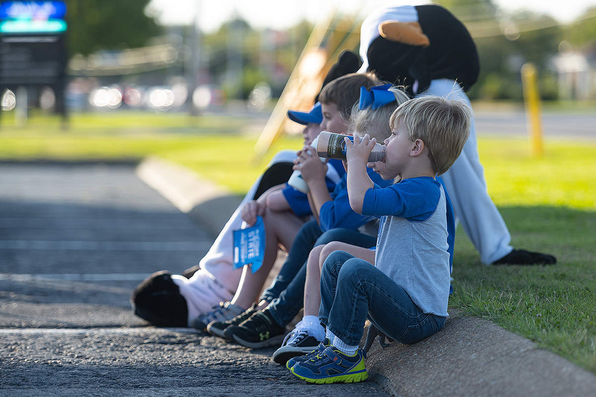 """Along with the MTSU Creamery cow, a group of children enjoy chocolate milk during the """"Moo-ving Happy Hour"""" homecoming event Thursday, Oct. 1, in the Greenland Drive parking lot adjacent to Murphy Center. They include Jackson Wright, 3, foreground, Addison Wright, 6, Mason Wright, 8, and Riggs King, 7. (MTSU photo by Cat Curtis Murphy)"""