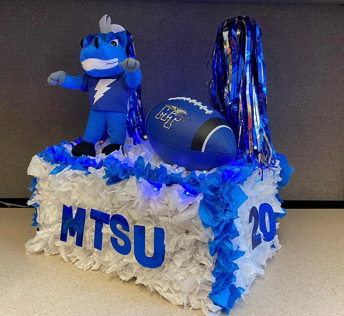 "A stuffed animal version of MTSU mascot Lightning stands on a scaled-down version of a Homecoming Parade float with True Blue pom poms and MT football — one of about five dozen of entries submitted by Blue Raider faithful for the virtual ""MTShUbox Parade"" event broadcast Saturday, Oct. 3, from outside the Alumni House on Middle Tennessee Boulevard on True Blue TV. (Submitted photo)"