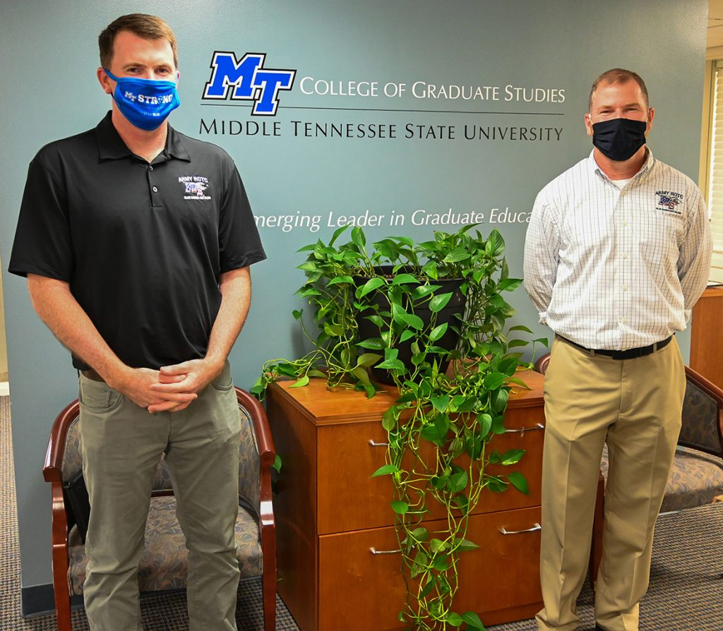 Lt. Col. Carrick E. McCarthy, left, and Marty Hill, right, of the Military Science Department pose in front of a wall decal in the College of Graduate Studies on Sept. 23, 2020. (MTSU photo by Stephanie Barrette)