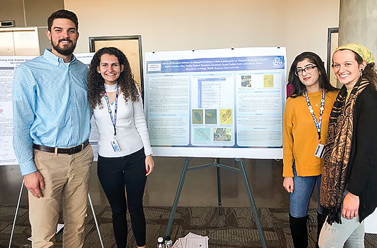 Members of MTSU's undergraduate research group SOAR, which stands for Student Organization for the Advancement of Research, smile with a project at the 2019 Undergraduate Research Center Fall Open House on Nov. 15, 2019 at MTSU. Standing, from left, are Nathan Smith, Radina Porashka, Sauleen Shamdeen and Mary Parsley. (MTSU photo by Jamie Burriss)