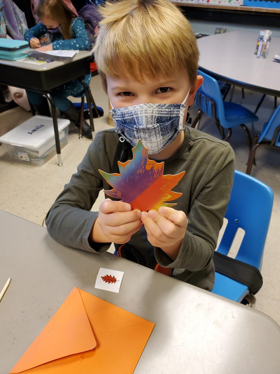 Brooks Bergsieker, a student in teacher Anne Mayes' class at Homer Pittard Campus School, holds a colorful leaf that was part of the items in the 80 harvest handbags made and delivered by MTSU School of Agriculture agritourism students. (Submitted photo by Campus School)