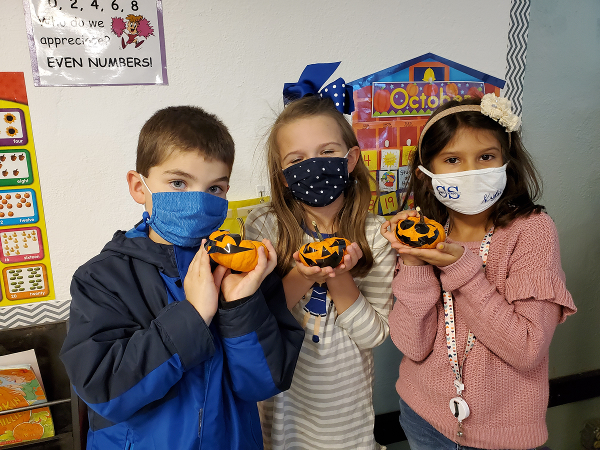 Homer Pittard Campus School first grade students Cooper McDevitt, left, Mary Bryant Vaughn and Kylie Medina display the handheld pumpkins, which were part of the Harvest Handbag items provided by the MTSU agritourism class. Black stickers were included, so the youngsters could make their own pumpkin faces. (Submitted photo by Homer Pittard Campus School)