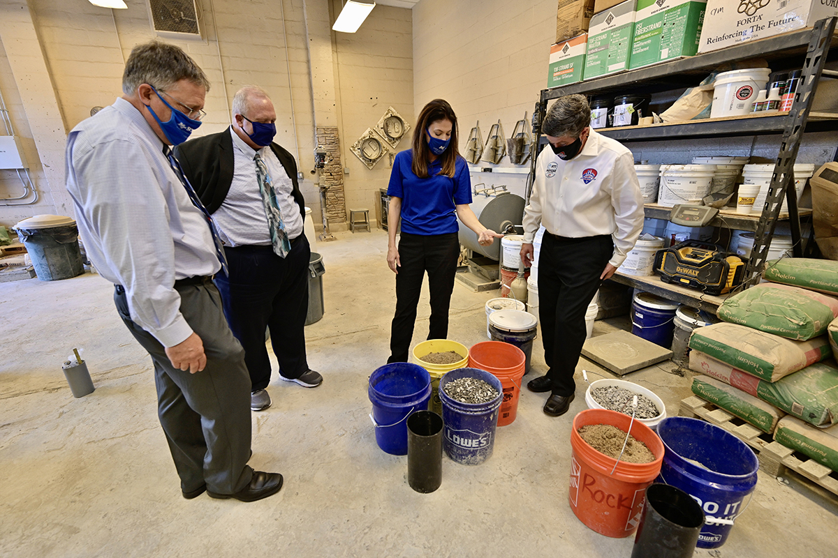 Heather Brown, second from right, MTSU concrete industry professor and former director of the School of Concrete and Construction Management, explains the ingredients from concrete mixes that were to be tested Monday, Nov. 9, inside a lab in the Voorhees Engineering Technology Building. Pictured, from left, are MTSU Provost Mark Byrnes; Bud Fischer, dean of the College of Basic and Applied Sciences; Brown; and Matt Crews, MTSU alumnus and CEO of the Music City Grand Prix. MTSU and the Grand Prix signed a memorandum of understanding Monday formalizing their partnership in support of the event, which includes the university's concrete program producing eco-friendly race barriers for the August 2021 race. (MTSU photo by Andy Heidt)