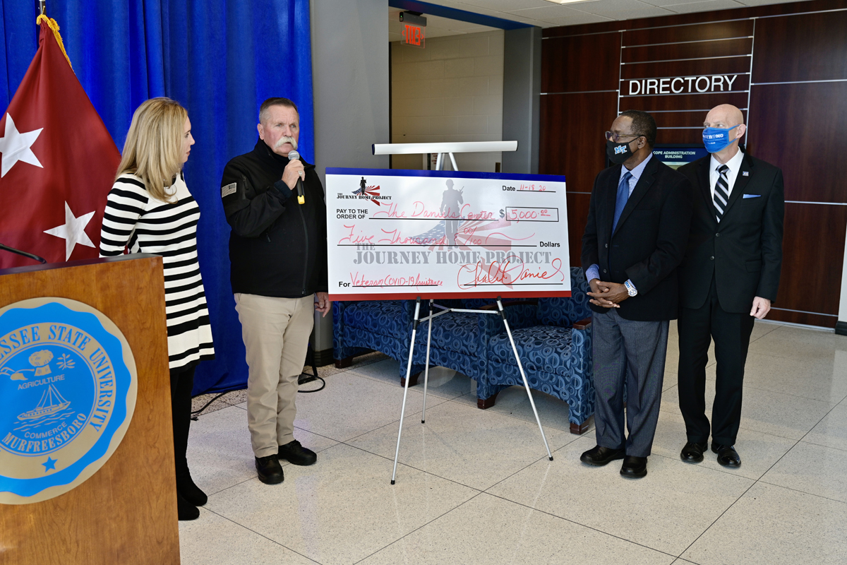 David Corlew, second from left, representing The Journey Home Project, presents a check for $5,000 to the Charlie and Hazel Daniels Veterans and Military Family Center Wednesday, Nov. 18, as part of the Graduating Veterans Stole Ceremony, held virtually for the honorees because of COVID-19 safety protocols, in the Cope Administration Building lobby. Looking on are Daniels Center Director Hilary Miller, left, MTSU President Sidney A. McPhee and Keith M. Huber, senior adviser for veterans and leadership initiatives and a retired U.S. Army lieutenant general. (MTSU photo by Andy Heidt)