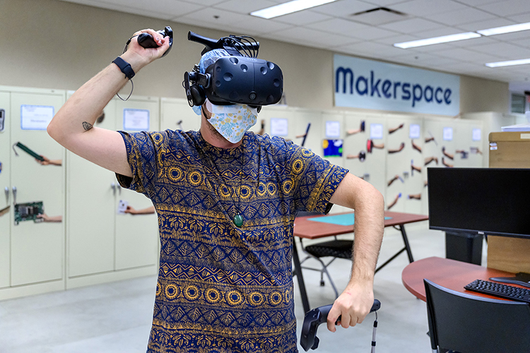 Keri LaPrairie, a student worker at Makerspace, demonstrates the virtual reality device. LaPrairie is wearing a hair covering and an additional mask between his face and the goggles to adhere to COVID-19 protocols. (MTSU Photo by J. Intintoli)