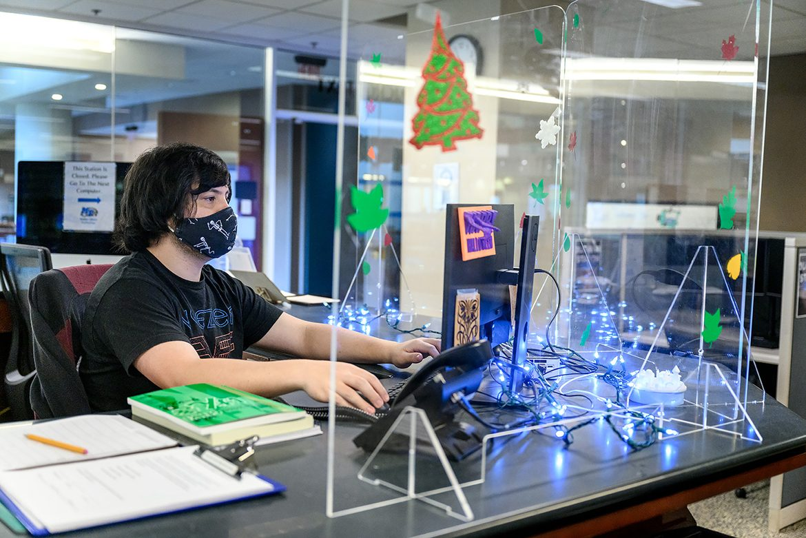Sean Strickland, a student worker at Makerspace, staffs the help desk behind Plexiglass shields while wearing a mask to adhere to pandemic protocols. Figurines made with Makerspace equipment adorn the shields. (MTSU Photo by J. Intintoli)