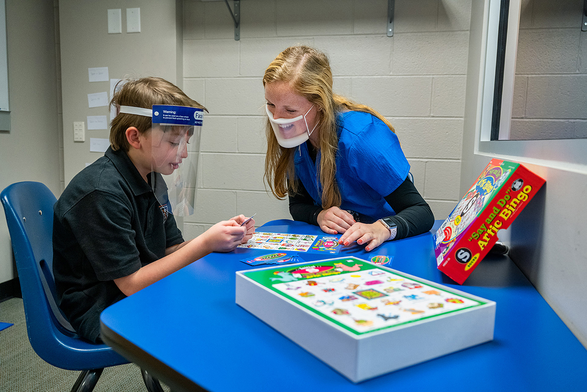 Madison Hoback, right, a student clinician at MTSU's Speech-Language-Hearing Clinic, wears a clear mask while helping client Riggs King, who is wearing a face shield. The clear protective devices help clients see the clinician's lips move and vice versa. (MTSU photo by Andy Heidt)