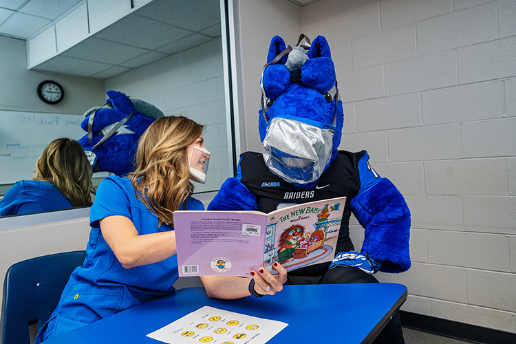 "Student clinician Amber Hayden, left, demonstrates the clear plastic mask she wears while helping clients at MTSU's Speech-Language-Hearing Clinic. MTSU's ""mask-ot,"" Lightning, is wearing a clear mask, as well. (MTSU Photo by Andy Heidt)."