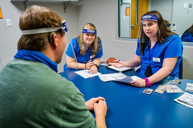 "Lindsey Lamb, back left, and Emily Hines, student clinicians, assist ""Keith,"" a pseudonym to protect the client's identity, while wearing clear face shields at the Speech-Language-Hearing Clinic at MTSU. The clear masks help clients see the clinicians' lips move and vice versa. (MTSU Photo by Andy Heidt)."