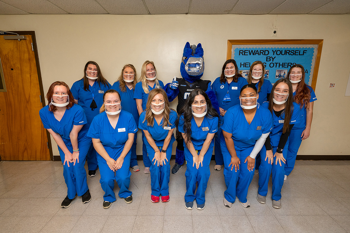 Student clinicians at MTSU's Speech-Language-Hearing Clinic pose for a group photo wearing their clear masks that enable clients to see how their lips move. Front row, l to r, Maggie Waller, Lexie Daddone, Amber Hayden, Rena Bamerini, Alana Crenshaw, and Delaney Freeze. Back row, l to r, Emily Hines, Lindsey Lamb, Avery Kaumayer, MTSU mascot Lightning, Kaylee Skipper, Madison Hoback, and Lana Chaney. (MTSU Photo by Andy Heidt)