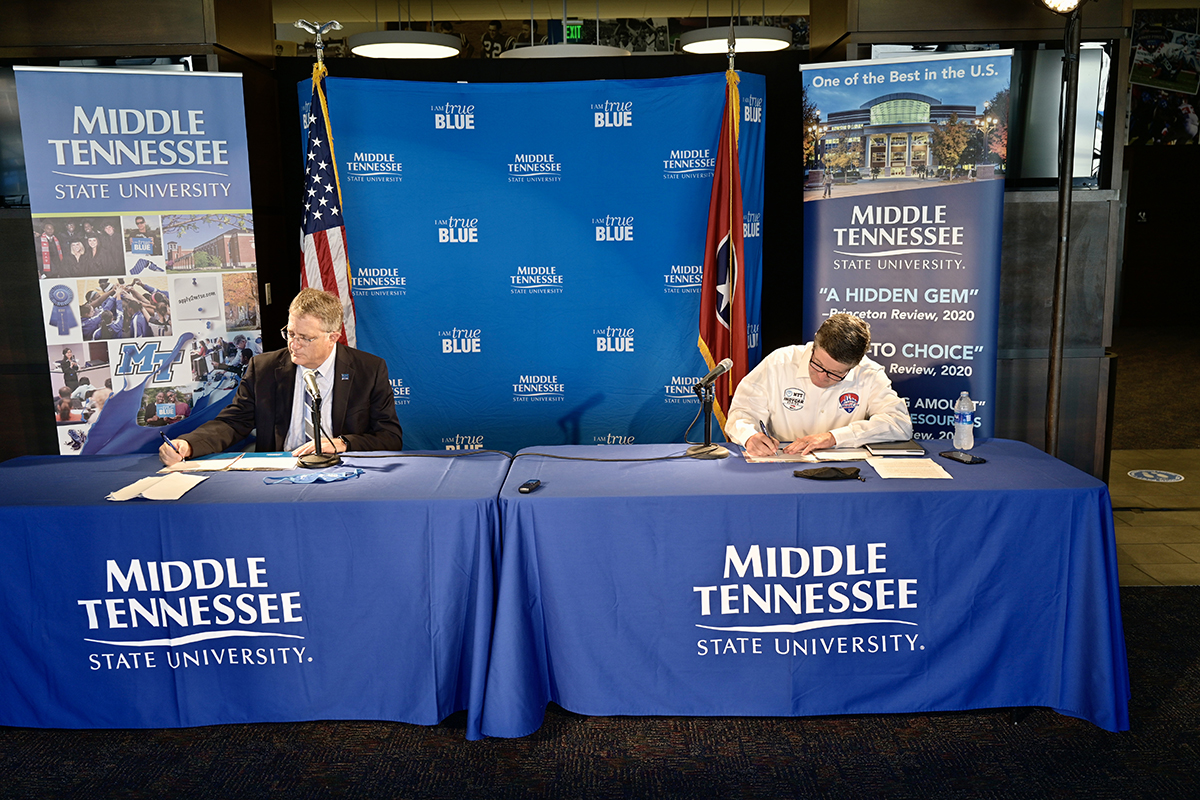 MTSU Provost Mark Byrnes, left, and Music City Grand Prix CEO and university alumnus Matt Crews sign the agreement, celebrating the partnership allowing the university's acclaimed concrete program and its students to create special environmentally conscious mixes for barriers and pit row for the August 2021 open-wheel race in downtown Nashville, Tennessee. Crews is a former Jones College of Business student and Blue Raider football player. (MTSU photo by Andy Heidt)