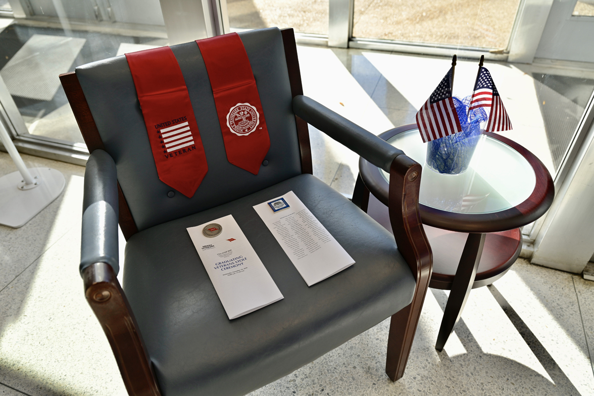 A red stole and a copy of the Graduating Veterans Stole Ceremony program sit on a chair in the Cope Administration Building lobby Wednesday, Nov. 18. Twelve senior veterans, who will graduate Saturday, Nov. 21, in ceremonies in Floyd Stadium, participated in the virtual ceremony. (MTSU photo by Andy Heidt)