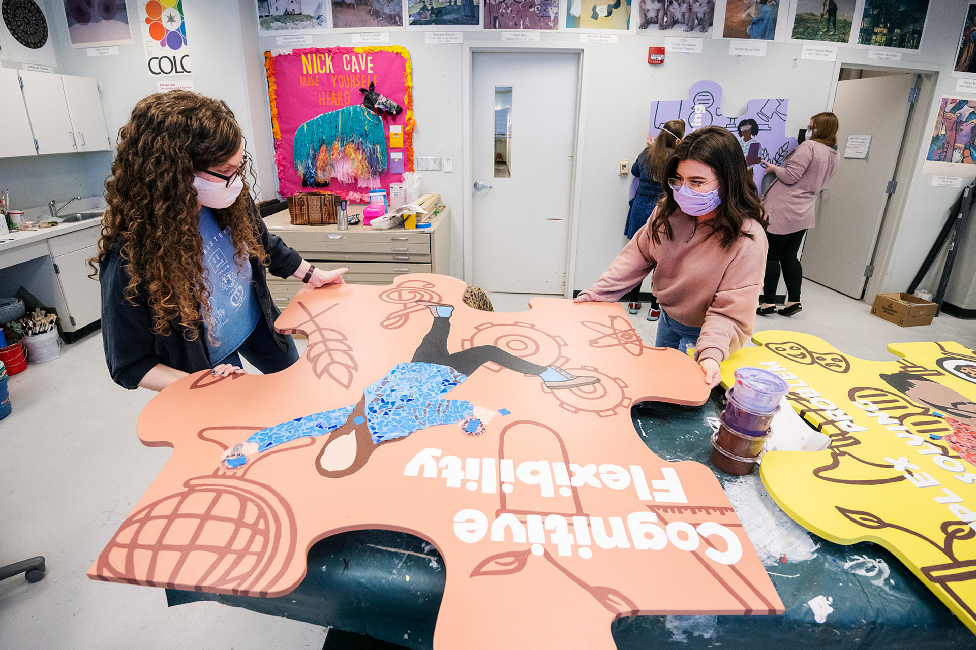 "MTSU senior art education majors Kaitlyn Estes, left, of Murfreesboro and Adriana Castro of Smyrna, Tenn., carefully move an oversized wooden puzzle piece for ""cognitive flexibility"" in Todd Hall Thursday, Nov. 19. The 10 different handcrafted puzzle pieces, touched up, with mosaics added, and ready for display, are part of a public art project collaboration between the College of Liberal Arts and the College of Basic and Applied Sciences to show students the interdisciplinary core skills they need for success. (MTSU photo by Andy Heidt)"