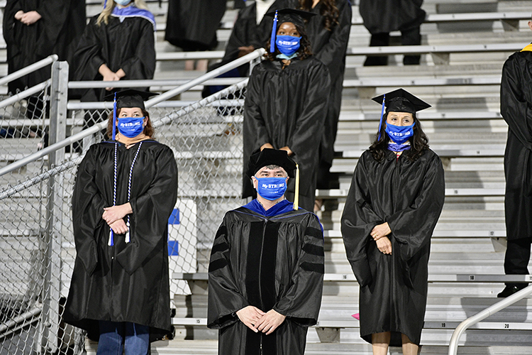 A group of MTSU students stand during a moment of silence at Floyd Stadium Saturday, Nov. 21, during the university's fall 2020 commencement ceremonies. MTSU, which held virtual graduations for its May and August graduates because of the pandemic, required strict mask, physical distancing and other health protocols for the graduates and limited their guests to help keep the three open-air events safer. (MTSU photo by Andy Heidt)