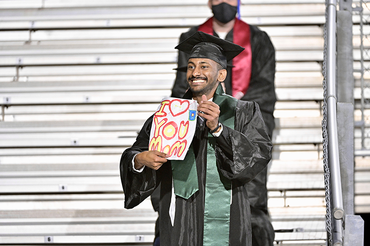 An MTSU student holds up a message of thanks as he's recognized on the Jumbotron at Floyd Stadium Saturday, Nov. 21, during the university's fall 2020 commencement ceremonies. MTSU, which held virtual graduations for its May and August graduates because of the pandemic, required strict mask, physical distancing and other health protocols for the graduates and limited their guests to help keep the three open-air events safer. (MTSU photo by Andy Heidt)
