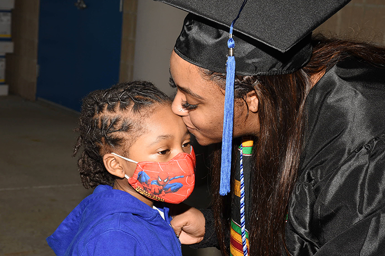 An MTSU student gives — and gets — encouragement from her little one in the concourse under Floyd Stadium Saturday, Nov. 21, before the university's fall 2020 commencement ceremonies. MTSU, which held virtual graduations for its May and August graduates because of the pandemic, required strict mask, physical distancing and other health protocols for the graduates and limited their guests to help keep the open-air event safer. (MTSU photo by GradImages)