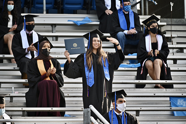 An MTSU student waves as she's recognized on the Jumbotron at Floyd Stadium during the university's fall 2020 commencement ceremonies last November. MTSU, which held virtual graduations for its May and August 2020 graduates because of the pandemic, held three outdoor events last fall. Spring 2021 graduates will return to Murphy Center May 7-9 for the first time since 2019 for a three-day, 10-event, socially distanced commencement weekend. (MTSU file photo by J. Intintoli)