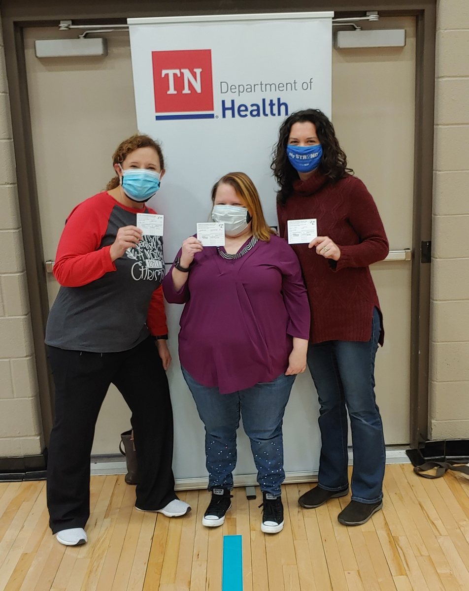 MTSU Pharmacist Tabby Ragland, left, pharmacy technician Shannon Shaffer and Health Promotion Director Lisa Schrader show their COVID vaccine reminder cards to get the second dose of the Moderna vaccine after receiving the first dose Wednesday, Dec. 23, at the Siegel High School Gym in Murfreesboro. About 12 MTSU staff members were among dozens of health care workers and first responders receiving the vaccine. (MTSU photo by Jason Schrader)