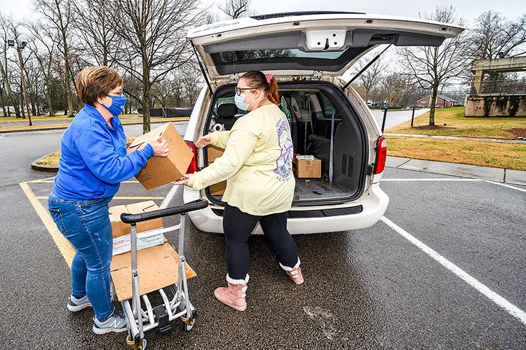 Tracy Read, left, Middle Tennessee State University's director of Parking and Transportation Services, and Jamie Chumbley, right, a dispatcher at Parking and Transportation Services, load a van with supplies while moving out of the current MTSU Parking Services Building on East Main Street on Dec. 16, 2020. (MTSU photo by Andy Heidt)