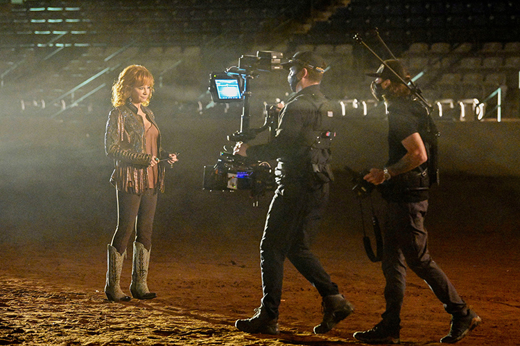 """Middle Tennessee State University alumnus Tony Reyes, steady camera operator, middle, and Shaun Silva, director, right, work with country music superstar Reba McEntire during the music video shoot for her new single with artist Cody Johnson """"Dear Rodeo"""" at MTSU's Tennessee Miller Coliseum in Murfreesboro, Tenn., on Oct. 1, 2020. (MTSU photo by Andy Heidt)"""