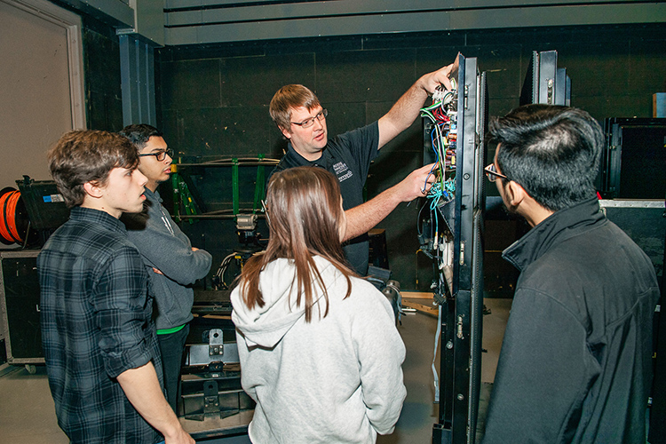 "Mike Forbes, Middle Tennessee State University assistant director of technical systems, works with students to deconstruct LED video display panels for use on the set of MTSU Theatre's production of ""Joseph and the Amazing Technicolor Dreamcoat"" on campus on March 15, 2018. Standing, from left, are Liam Nelson, Mina Ghattas, Sydney Penn, Forbes and Minh Phan. (MTSU file photo by Andy Heidt)"